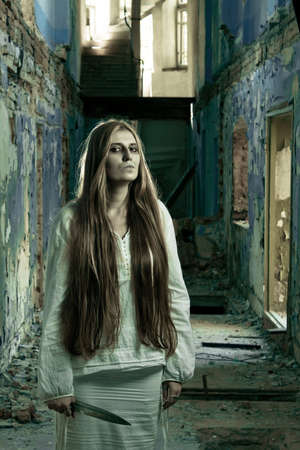 zombie girl in abandoned building with knife photo