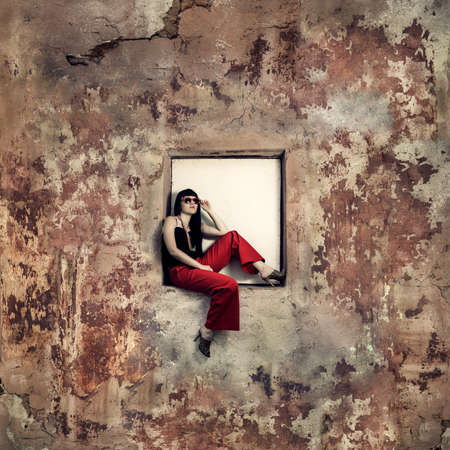 dappled: girl sitting on window of an abandoned building