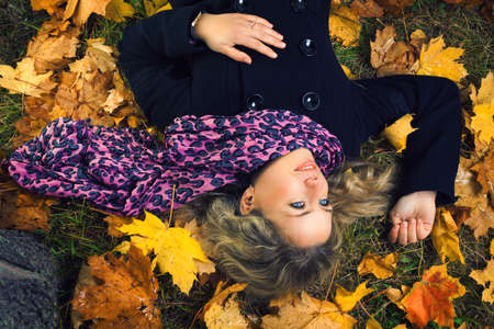 beautiful girl in scarf lying under autumn tree photo