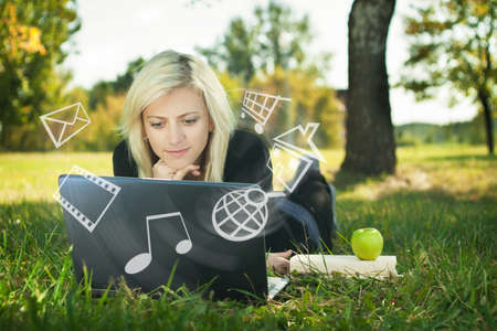 music book: girl in park with laptop multimedia concept Stock Photo