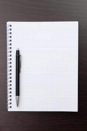 lapiceros: cuaderno en blanco y un bol�grafo negro sobre la mesa