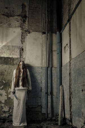 zombie girl with loong hair in an abandoned building holding knife photo