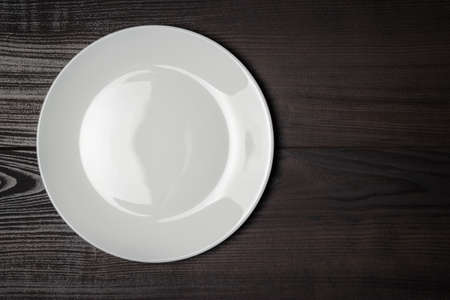 wooden plate: white plate on the wooden brown table Stock Photo