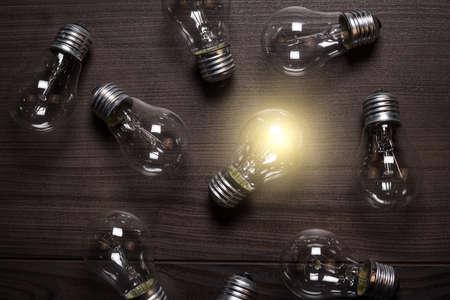leuchtende Glühbirne über Holzuntergrund Einzigartigkeit Konzept