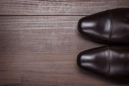 Mann im braunen Schuhen stand auf dem Holzboden Hintergrund Standard-Bild