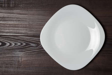 cooking utensils: square plate on the wooden brown table