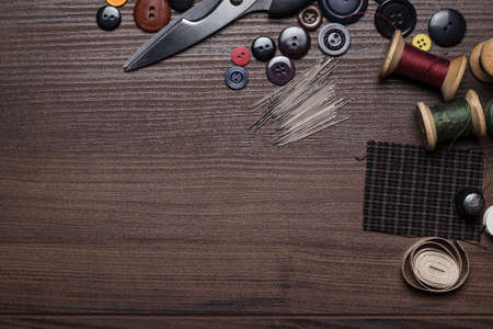 tailor measure: needles threads and buttons  on brown wooden table Stock Photo