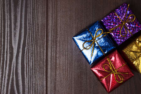 colorful present boxes over brown wooden background photo