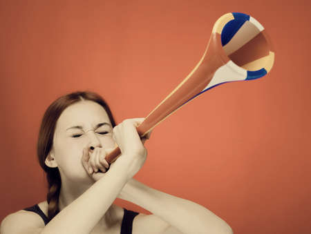 young girl blowing the trumpet over red background Stock Photo - 16711036