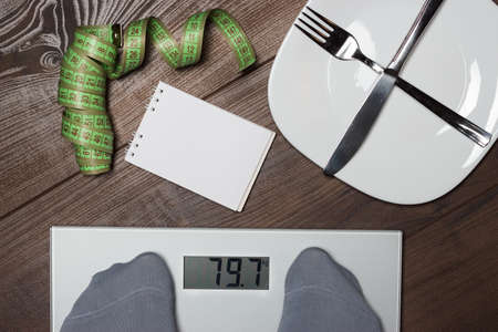 Dieting concept with scales on the wooden floor photo