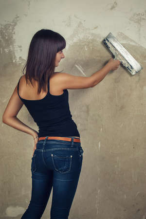 sexy construction worker: beautiful young girl holding spatula over grunge background Stock Photo