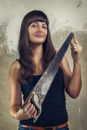 beautiful young girl holding saw over grunge background photo