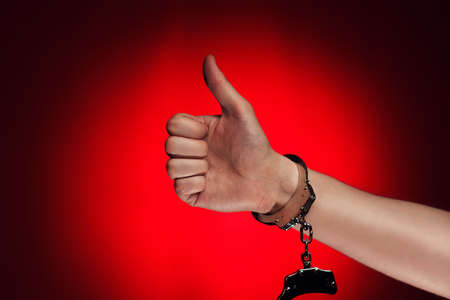 shackles: hand with thumb up and handcuffs opened concept