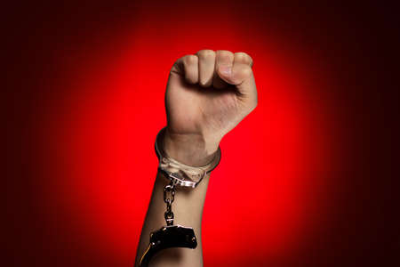 fist and handcuffs opened over red background concept photo