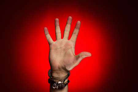 wristlets: hand in handcuffs over red background concept