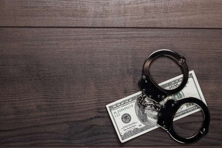 wristlets: handcuffs and one hundred dollars on wooden table