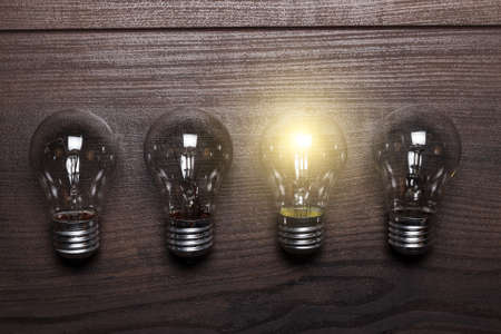uniqueness: bulb uniqueness concept on brown wooden background