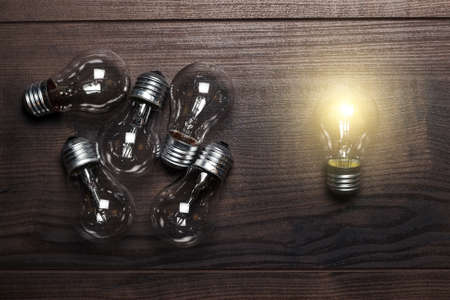 unique  difference: bulbs uniqueness concept on brown wooden background