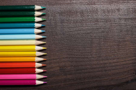 multicolored pencils on brown wooden table background photo