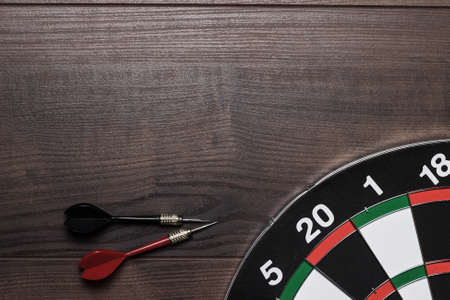 target and two darts on the wooden table photo