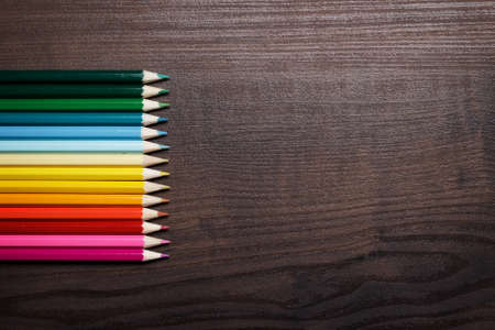 design tools: multicolored pencils over brown table background Stock Photo