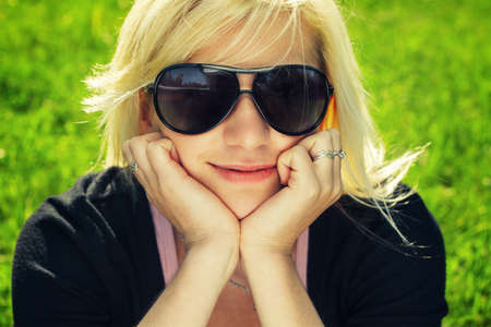 young girl in sunglasses sitting on grass photo