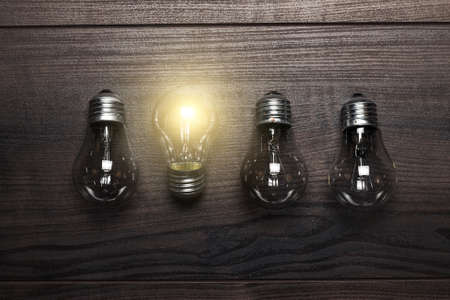 idea light bulb: glowing bulb uniqueness concept on wooden background Stock Photo