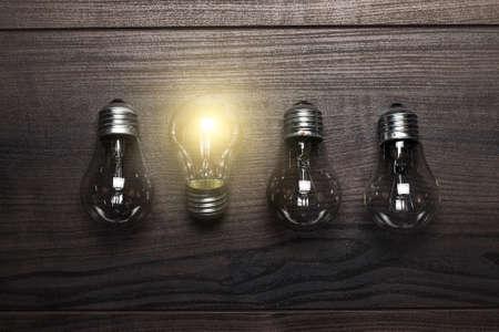 leuchtende Glühbirne Einzigartigkeit Konzept auf Holzuntergrund