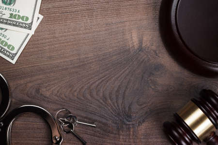 wristlets: handcuffs gavel and money on wooden background
