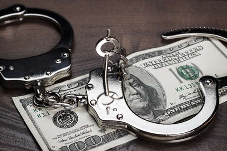 wristbands: handcuffs and one hundred dollars on the table Stock Photo