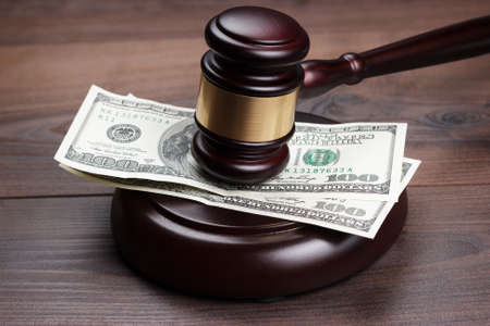 unfairness: judge gavel and money on brown wooden table Stock Photo