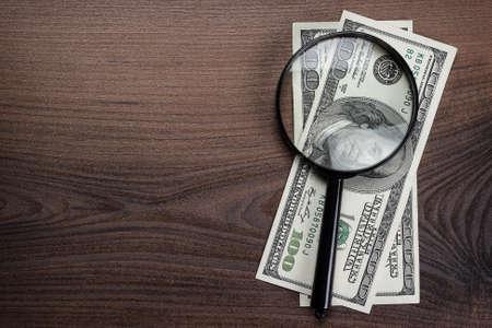 dinero falso: lupa y dinero en el fondo de madera