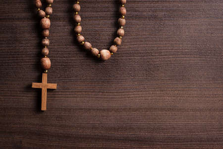 catholic symbols: cross over brown wooden background