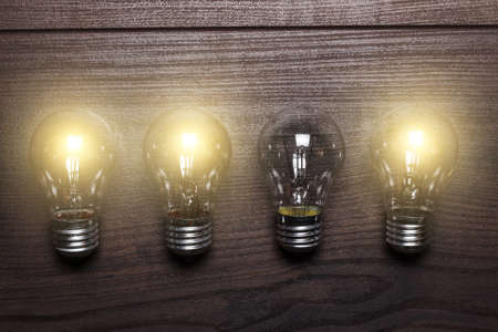 burned out: glowing bulbs weak link concept on wooden background Stock Photo