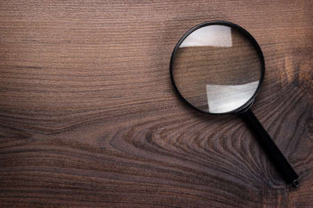 find glass: magnifying glass on wooden background
