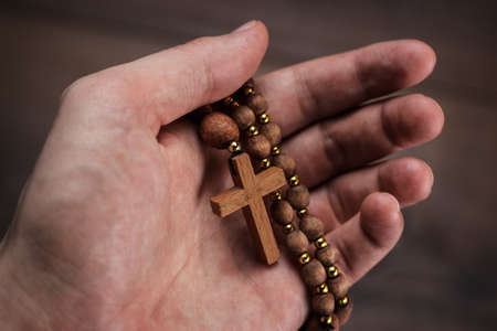 wooden cross in hand with focus on the cross
