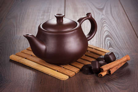 teapot with hot tea and cinnamon sticks photo