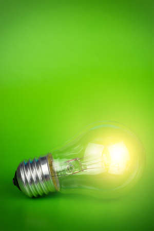 glowing light bulb over green background photo