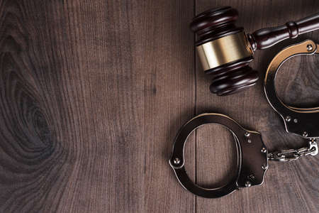fraud: handcuffs and judge gavel on wooden background Stock Photo