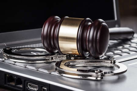 handcuffs and judge gavel on computer concept photo