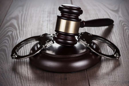 wristbands: handcuffs and judge gavel on brown table Stock Photo