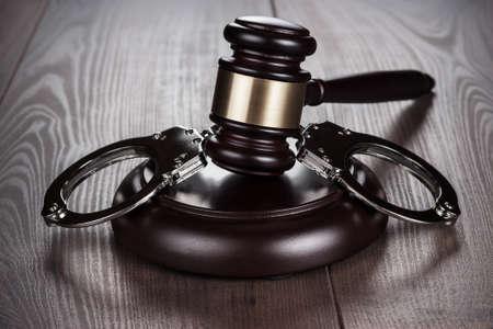 handcuffs and judge gavel on brown table Zdjęcie Seryjne