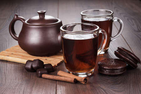 teatime: cup of tea with cinnamon sticks and teapot on the table Stock Photo