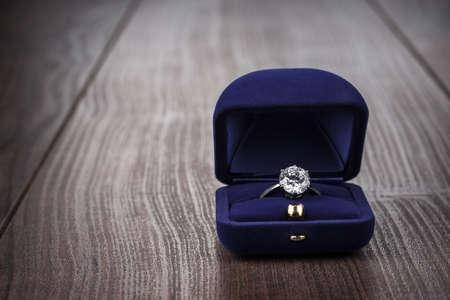 verlobung: Ring in der Box auf Holztisch