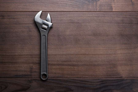 adjustable wrench on the brown wooden background photo