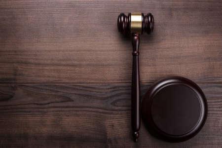 茶色の木製の背景に裁判官の小槌