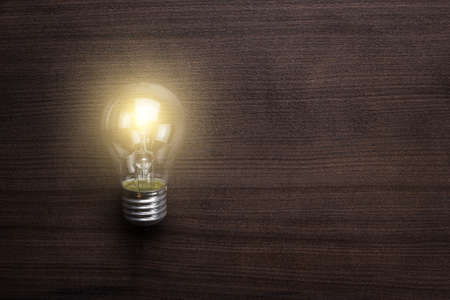 electric bulb: glowing bulb on the brown wooden background