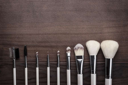 white make-up brushes on brown wooden background photo