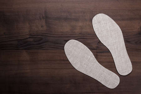 inner wear: grey insoles for shoes over wooden background