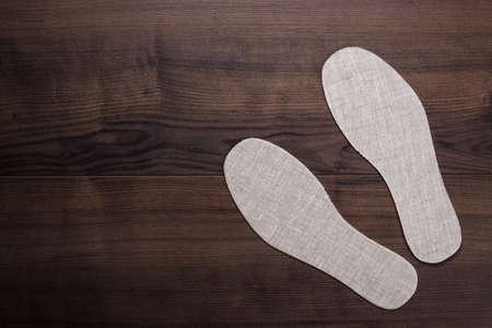 grijze inlegzolen voor schoenen over houten achtergrond